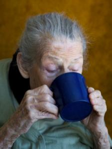 elderly woman drinking from a mug