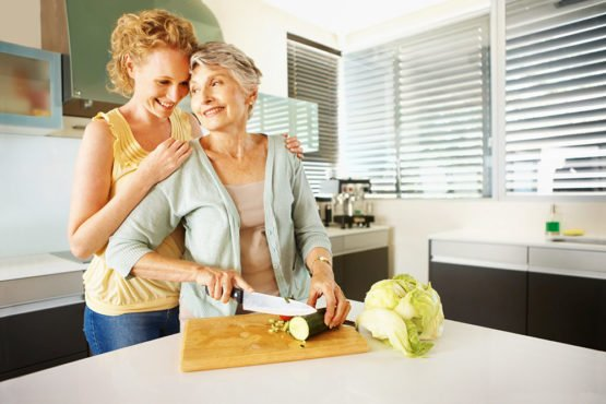senior cooking with family member