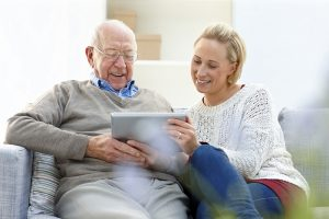 family caregiver helping senior with a tablet