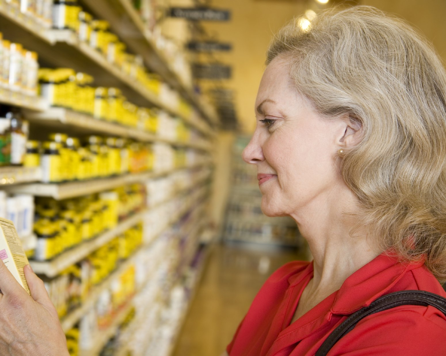elderly woman looking at vitamins on the shelf