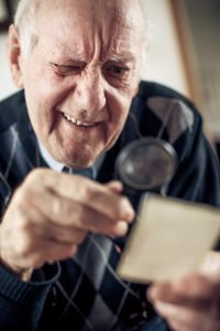 older man using a magnifying glass to read