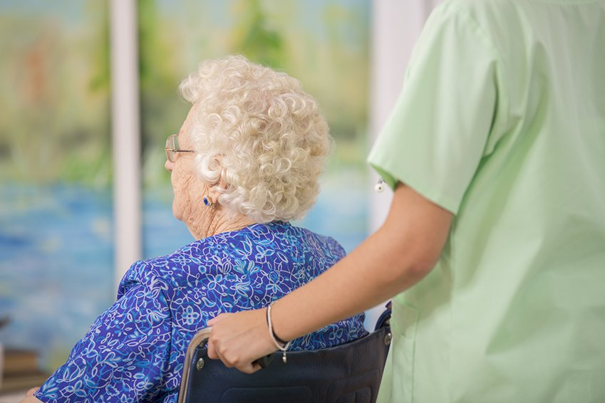 senior in a wheelchair being helped by caregiver