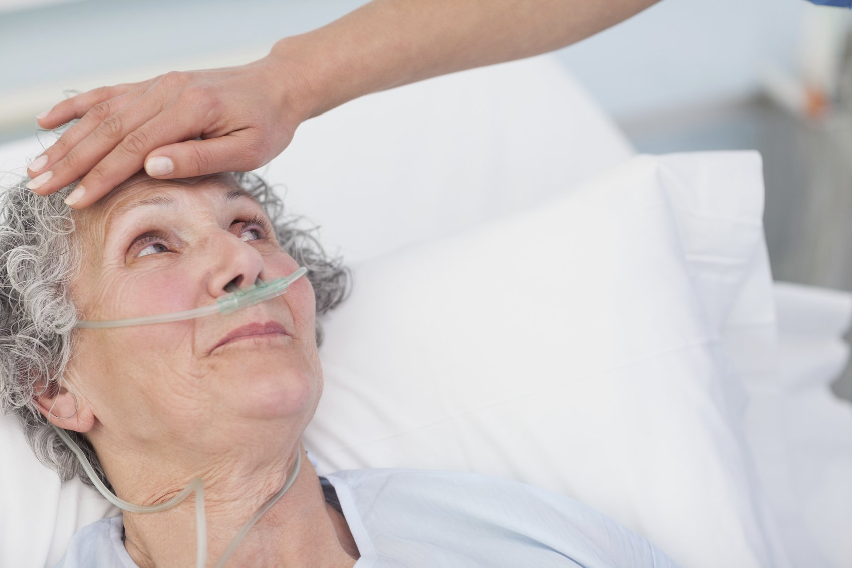 nurse feeling senior patient's forehead