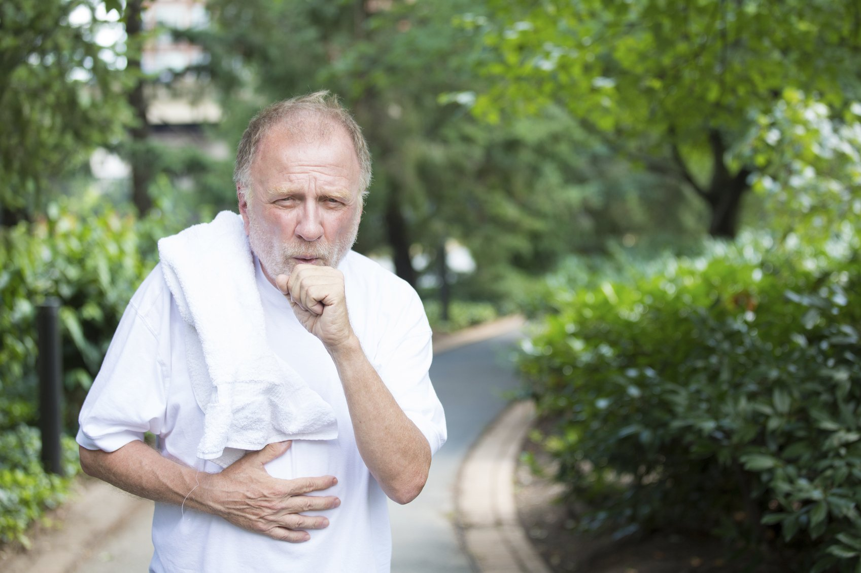 elderly man covering his mouth to cough