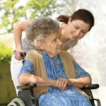 caregiver pushing older woman in a wheel chair