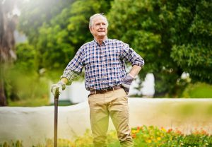 senior-man-with-cane-outside-gardening