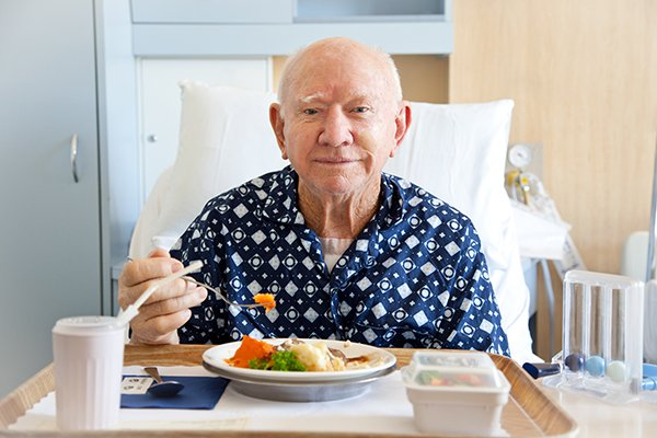Senior man patient in hospital eating lunch