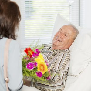 senior-man-receiving-flowers-in-bed