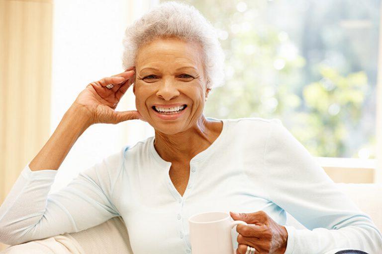 Happy senior woman drinking coffee