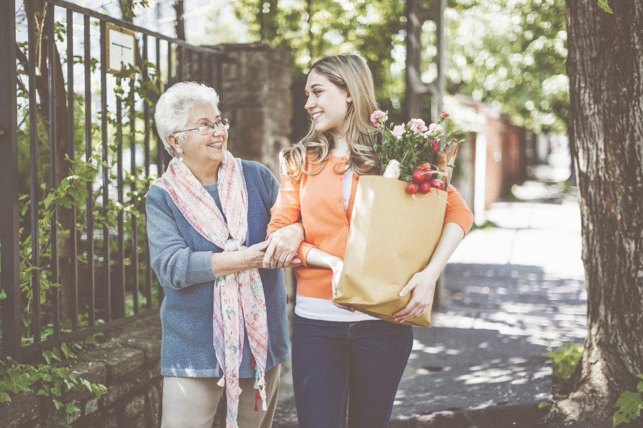 family caregiver holding groceries for senior loved one
