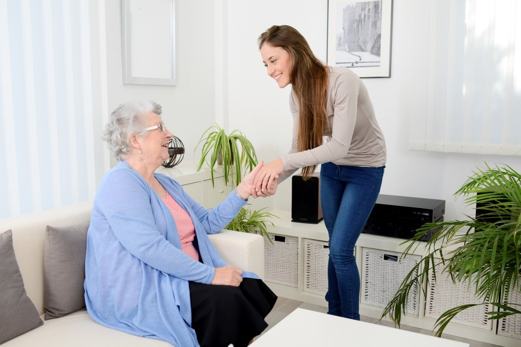 caregiver holding hands with senior