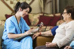 caregiver taking a client's blood pressure