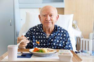 senior man eating in a hospital bed