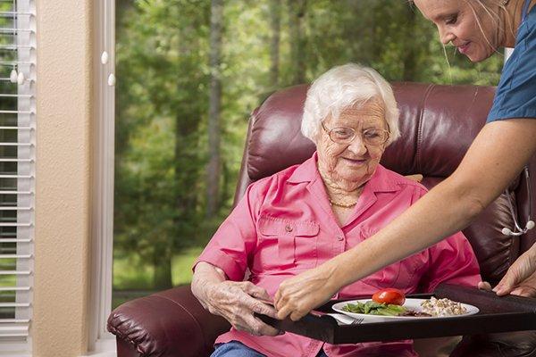 happy-caregiver-serving-senior-woman