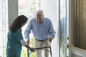 Caregiver helping elderly man with Lewy Body Dementia.