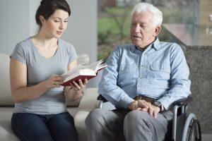 caregiver reading to senior man in wheelchair
