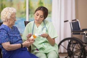Caregiver helping senior with medication