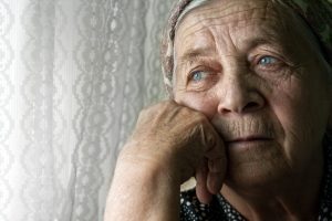Senior woman appears sad as she looks out the window